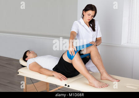 Female Therapist Helping Young Man While Exercising In Hospital - Stock Photo
