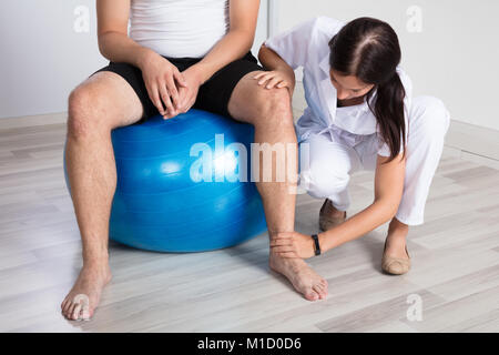 Young Female Physiotherapist Examining Man's Injured Leg In Clinic - Stock Photo