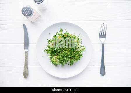 Top view plate with fresh organic sprout micro greens served with cutlery and herbs on the white wooden table. Healthy Raw diet food concept. Copy spa