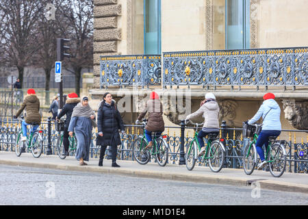 A group of women with matching beret hats cycle aroud Paris on bicycles, France - Stock Photo