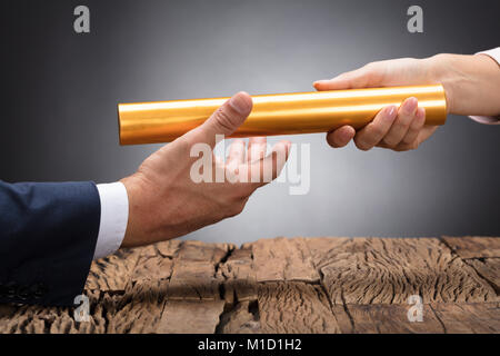 Close-up Of A Businessperson's Hand Passing Baton On Wooden Desk - Stock Photo