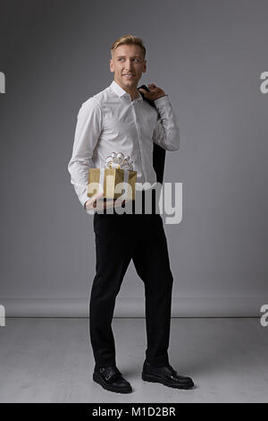 Smiling businessman holding present - Stock Photo