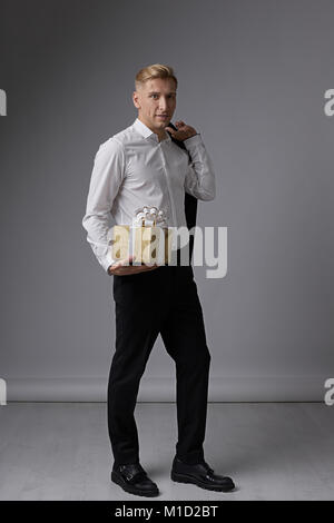 Businessman holding present - Stock Photo