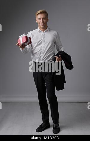 Stylish businessman holding gift box  - Stock Photo