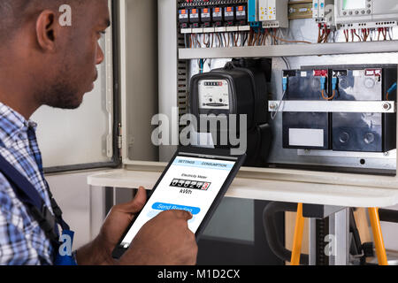Male Technician Doing Meter Reading Using Tablet - Stock Photo
