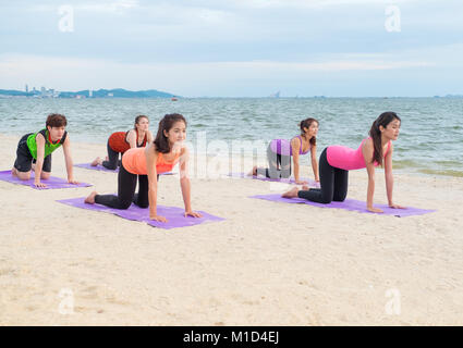 Yoga class at sea beach in evening sunset ,Group of people doing cat poses with clam relax emotion at beach,Meditation - Stock Photo