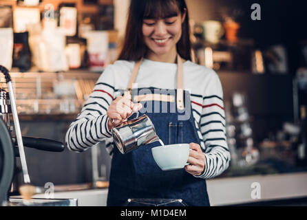Asia woman barista pour milk into hot coffee cup at counter bar in front of machine in cafe restaurant,Food business - Stock Photo