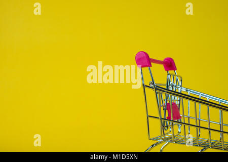 Shopping cart or supermarket trolley on yellow background, business finance shopping concept idea. - Stock Photo