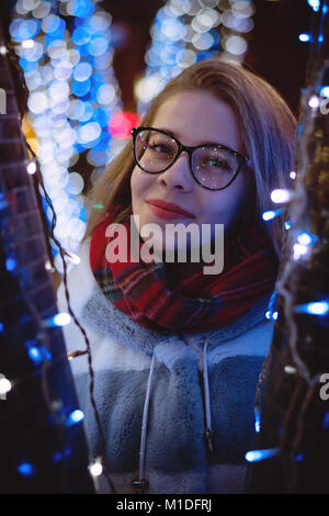 A young attractive girl in glasses and a warm scarf walks at the city fair. She smiles. Portrait at night among - Stock Photo