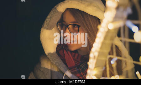 A young attractive hipster girl in glasses and a warm scarf walks by the mall on a holiday. She smiles. Portrait - Stock Photo