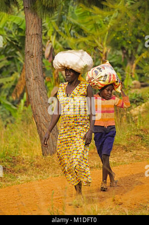 Rural Ugandan woman and young boy carrying sacks of produce on their heads in Crater Lakes district of Uganda, - Stock Photo