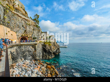 Tourists walk the path and enter the tunnel on the coast of Monterosso al Mare, Cinque Terre Italy, with the Monterosso - Stock Photo