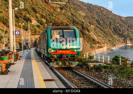 A train travels into the Monterosso al Mare train station on the Cinque Terre coast of Italy as travelers sit and - Stock Photo