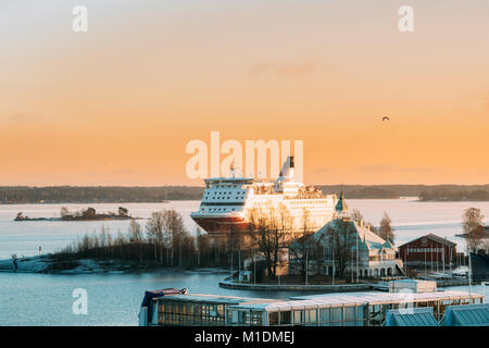 Helsinki, Finland. View Of Modern Ferry Ferryboat Sailing Near Blekholmen Valkosaari Island On Background Of Sunset - Stock Photo