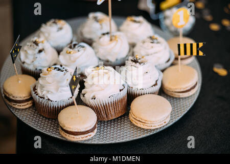 Dessert Sweet Tasty Cupcakes And Macarons In Candy Bar On Table. Delicious Sweet Buffet. Wedding Decorations - Stock Photo