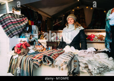 Helsinki, Finland - December 11, 2016: Woman Selling Scarves At European Winter Christmas Market. - Stock Photo