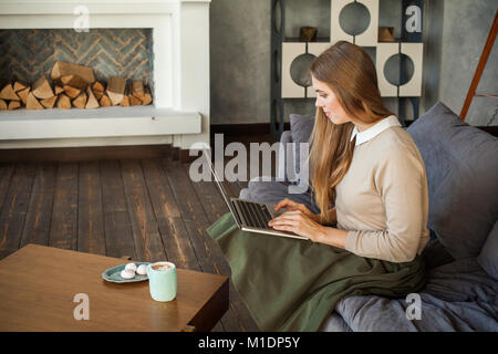 Young Businesswoman Using Laptop and Sitting on Sofa at Home Office - Stock Photo