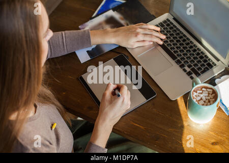Young Designer Woman sitting at Home Office Desk and Using Graphic Tablet and Laptop - Stock Photo