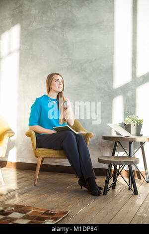 Cheerful Woman with Book and Laptop at Home Office. Woman Working with New Startup Project in Modern Loft - Stock Photo