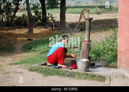 Woman washing the clothes at water pump in a rural area of Nepal on the border with India - Stock Photo