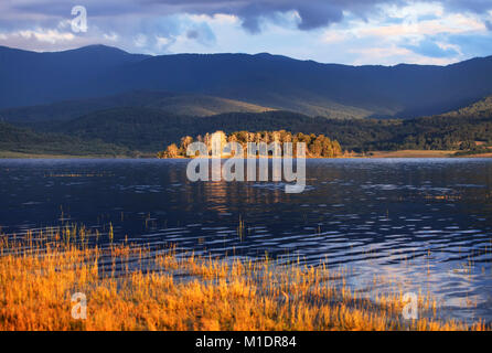 golden sunset over the lake and small island in bulgaria - Stock Photo