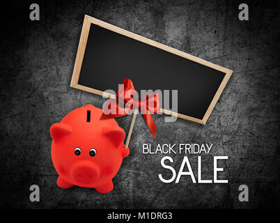 Black Friday sale text blackboard and piggy bank with red ribbon bow on black background - Stock Photo