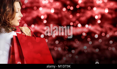 christmas shopping, woman with bag on red blurred bright lights background, banner template with copy space - Stock Photo