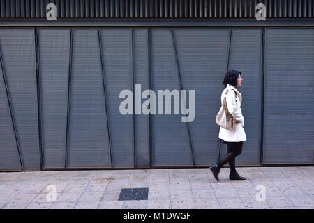 woman walking next to an iron texture wall - Stock Photo
