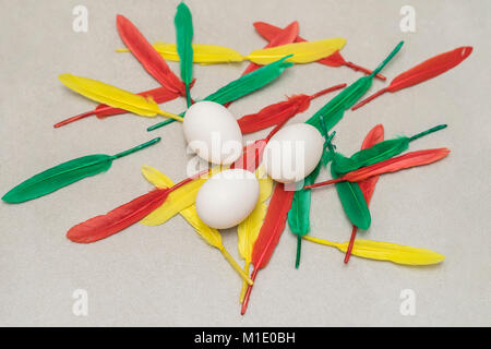 Natural white chicken eggs, green, red and yellow feathers on grey stone background. Easter still life, spring, - Stock Photo
