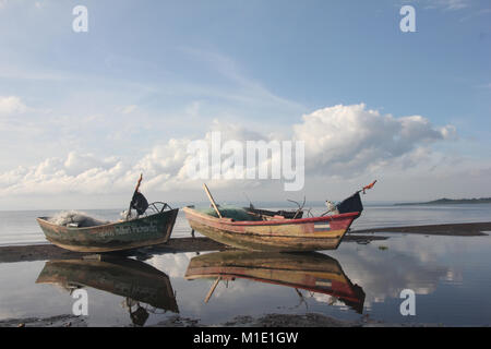 boats laying at the beach of a lacke in Nicaragua. Boats reflecting in the water on a sunny morning. - Stock Photo