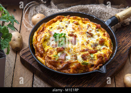 French omelette Savoyarde with bacon, cheese and leeks in fry pan, rustic - Stock Photo