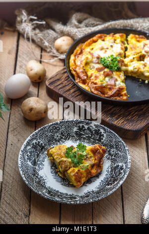 A piece of french baked omelette Savoy with ham, cheese, potato and leek on a plate, rustic style, top view - Stock Photo