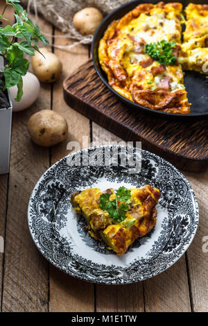 A piece of french baked omelette Savoyarde with ham, cheese, potato and leek on a plate, rustic style, top view - Stock Photo