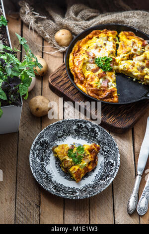 Omelette with bacon, potato, leeks and cheese on a plate, top view - Stock Photo