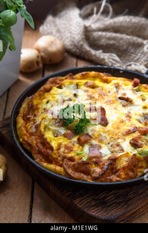 Baked omelette with bacon and cheese in a pan, close view - Stock Photo