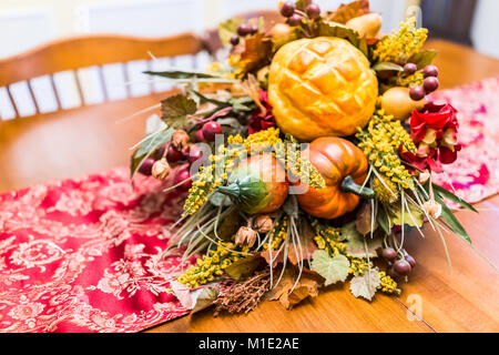 Closeup of Thanksgiving fall autumn fake cornucopia decoration on wooden table with red tablecloth in dining room - Stock Photo