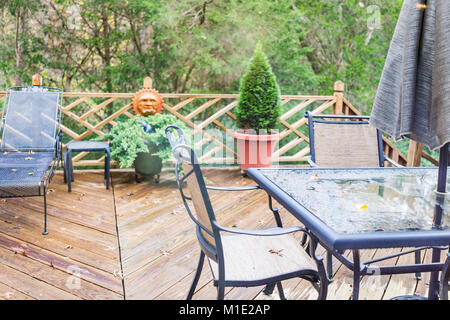 Closeup of wooden deck of house with many green plants, trees, tables, chairs, on rainy overcast day, decorations - Stock Photo