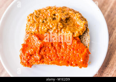 Closeup of slice piece of whole wheat sprouted toasted grain bread on plate with orange red bell pepper vegetable - Stock Photo
