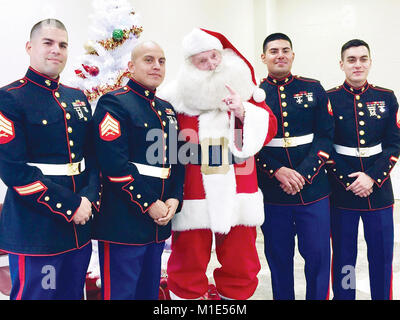Pictured from left to right are Sgt. Sanchez, Sgt. Diaz-Rodriquez, Cpl. Rodriguez and Sgt. West standing with Santa - Stock Photo