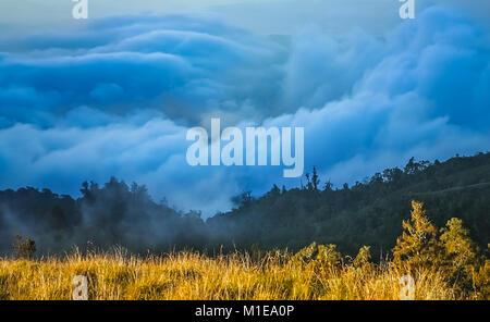 Dense clouds below the top of a ridge of Gunung Rinjani volcano in Lombok island, Indonesia - Stock Photo
