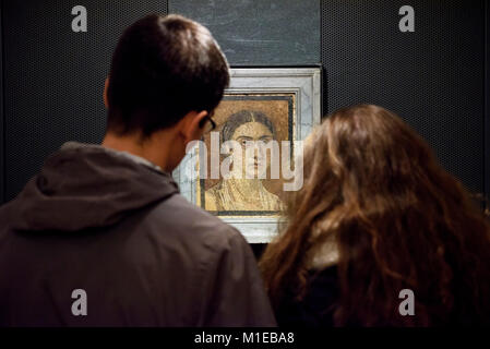 Naples. Italy. Visitors looking at Roman mosaic female portrait, from Pompeii. Museo Archeologico Nazionale di Napoli. - Stock Photo