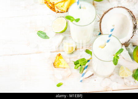 Tropical cocktail, pina colada, pineapple and coconut mojito or smoothies, with lime and mint, on a light blue background - Stock Photo