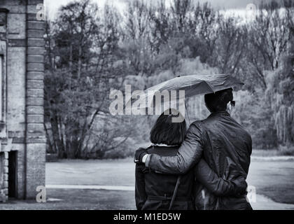 Young couple walk in the rain under an umbrella at Wrest Park, black and white image - Stock Photo