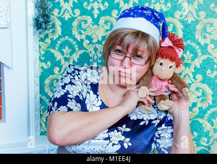 Girl in Santa hat sitting near the fireplace at home, laughing and holding a toy monkey - Stock Photo