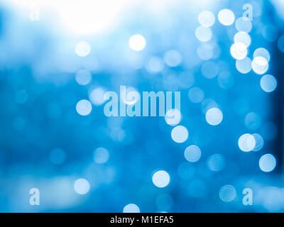 Bokeh effect of raindrops on a window. Blue comes from the sky in the background. - Stock Photo