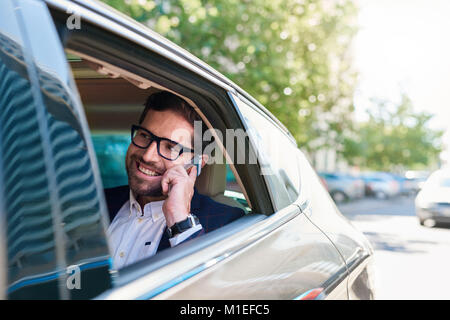 Smiling businessman driving through the city talking on a cellphone  - Stock Photo