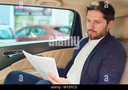 Businessman reading paperwork while being driven through the city  - Stock Photo