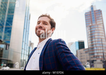 Successful young businessman smiling confidently while standing in the city - Stock Photo
