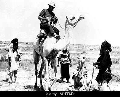 Black and white image depicting four men and two camels, three men in African clothing, one holding the lead of - Stock Photo