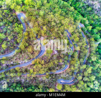 Frequent sharp turns on mountain remote road negotiating steep hills side of gum-tree covered creek in national park of Australia. Aerial view of pass